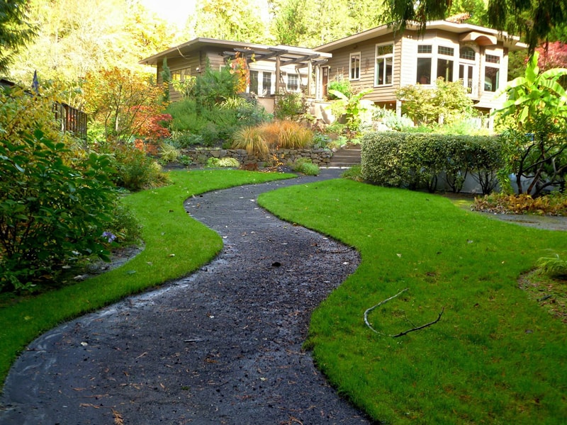 This simple path to the house, winding its way through lush green landscape is the perfect addition to the secluded location of this home..
