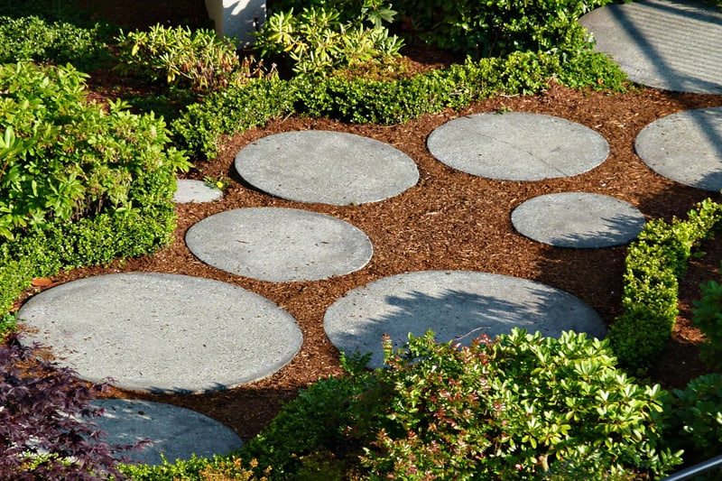 Round shaped, different sized concrete tiles surrounded by mulch, make this a visually appealing walkway.