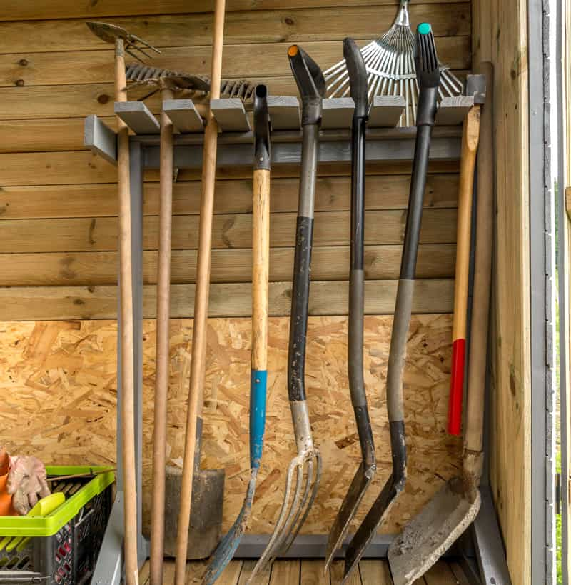 Wooden rack with garden tools and equipment for an organized shed