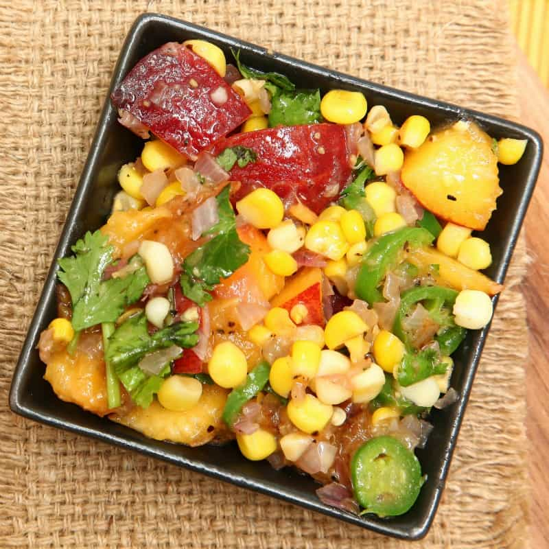 Peach and corn salsa on table, ready to eat.