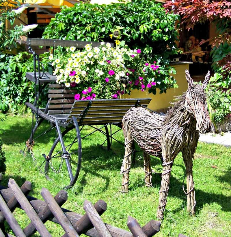 Garden decor: wicher donkey pulling flower filled cart.