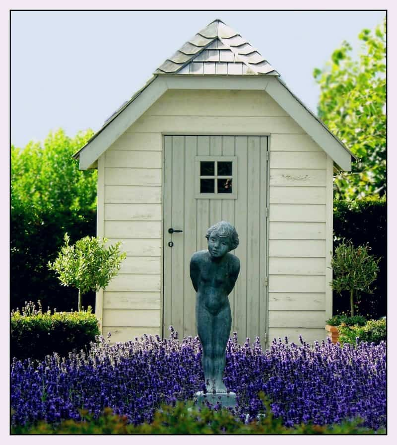 Smal shed with lavender flowers and a statuette