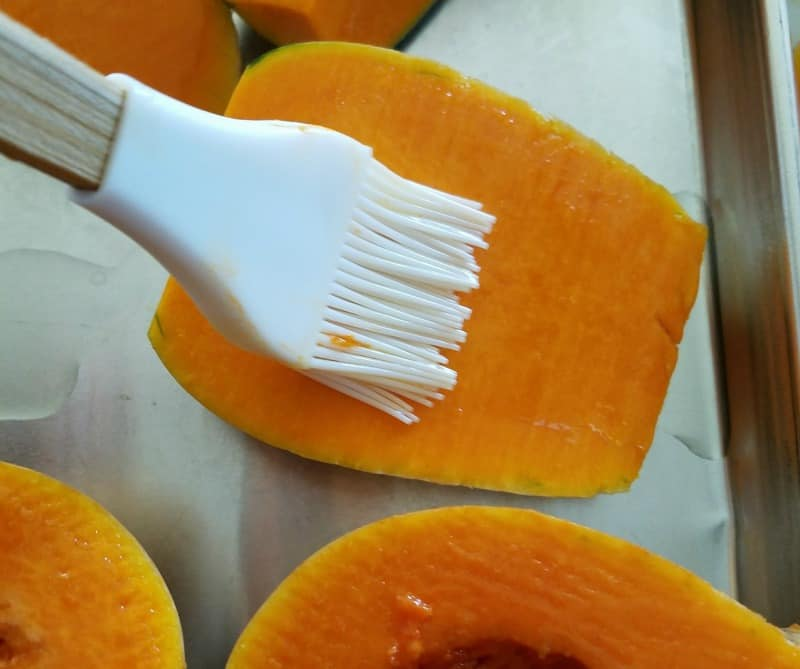 Brushing oil on squash before putting it in the oven