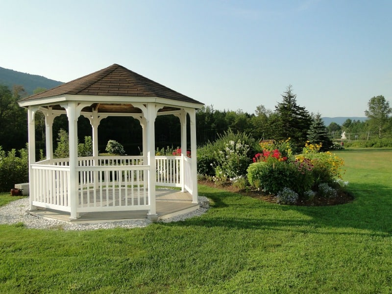 White gazebo with a splash of color from some shrubs and colorful flowers