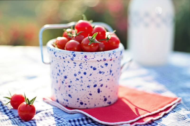 Ripe cherry tomatoes in a white bucket