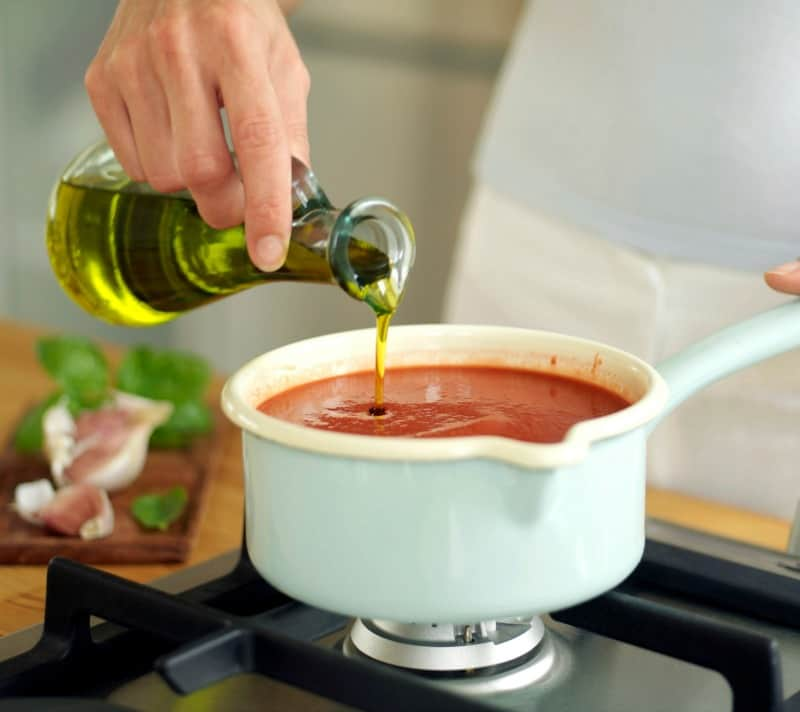 A bowl of tomato soup on the stove, and hand pouring oils in the soup