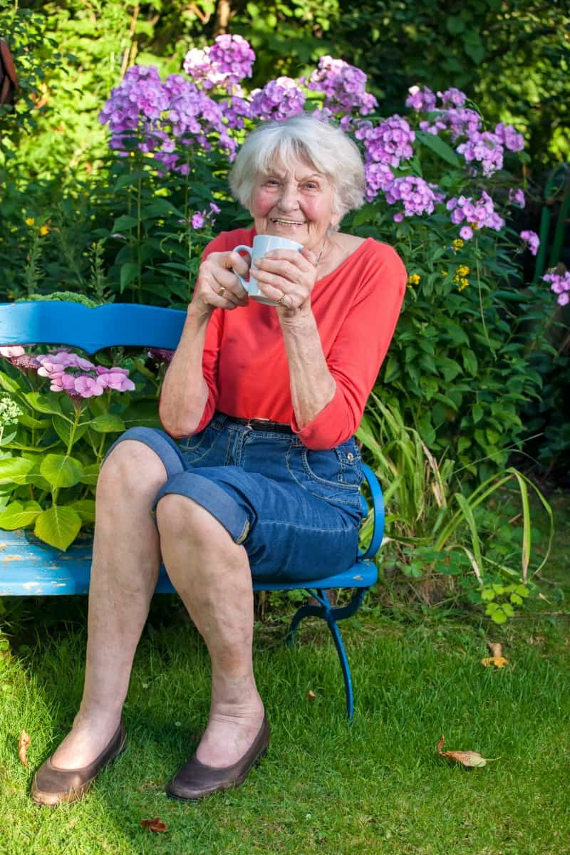 Grandma enjoying a cup of tea on a bench in her garden