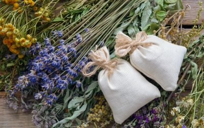 A bunch of healing herbs and sachets on wooden table, ready to make dream herbal pillows