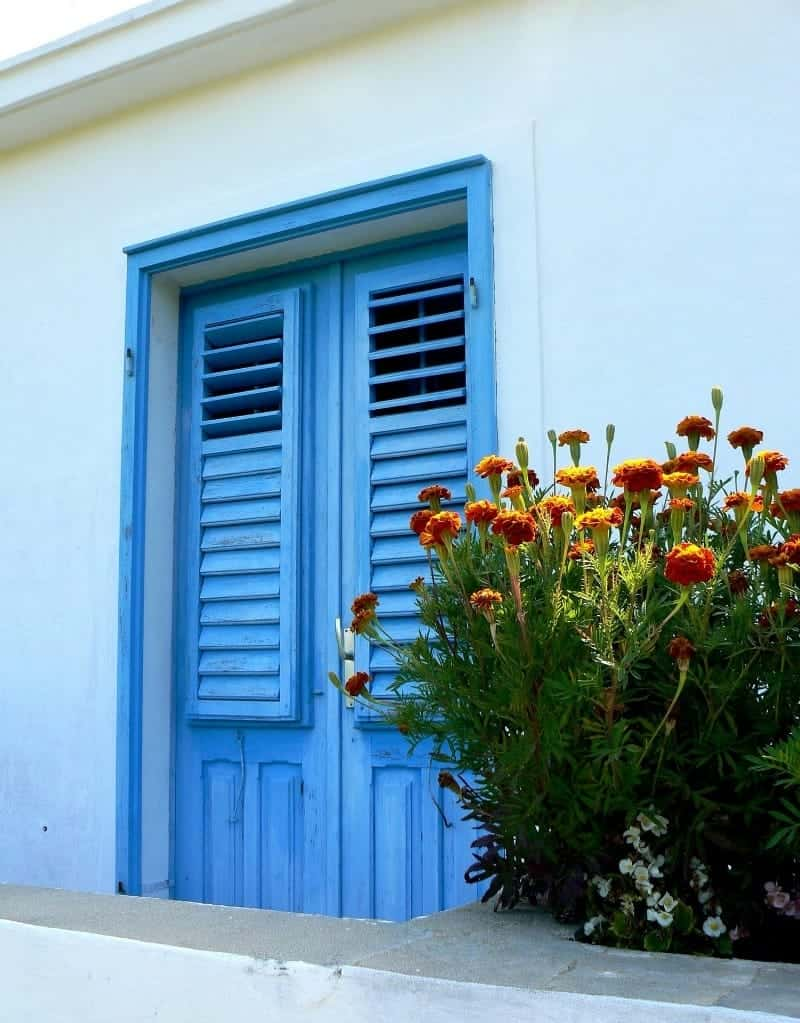 Bright blue front door and a colorful flower bouquet