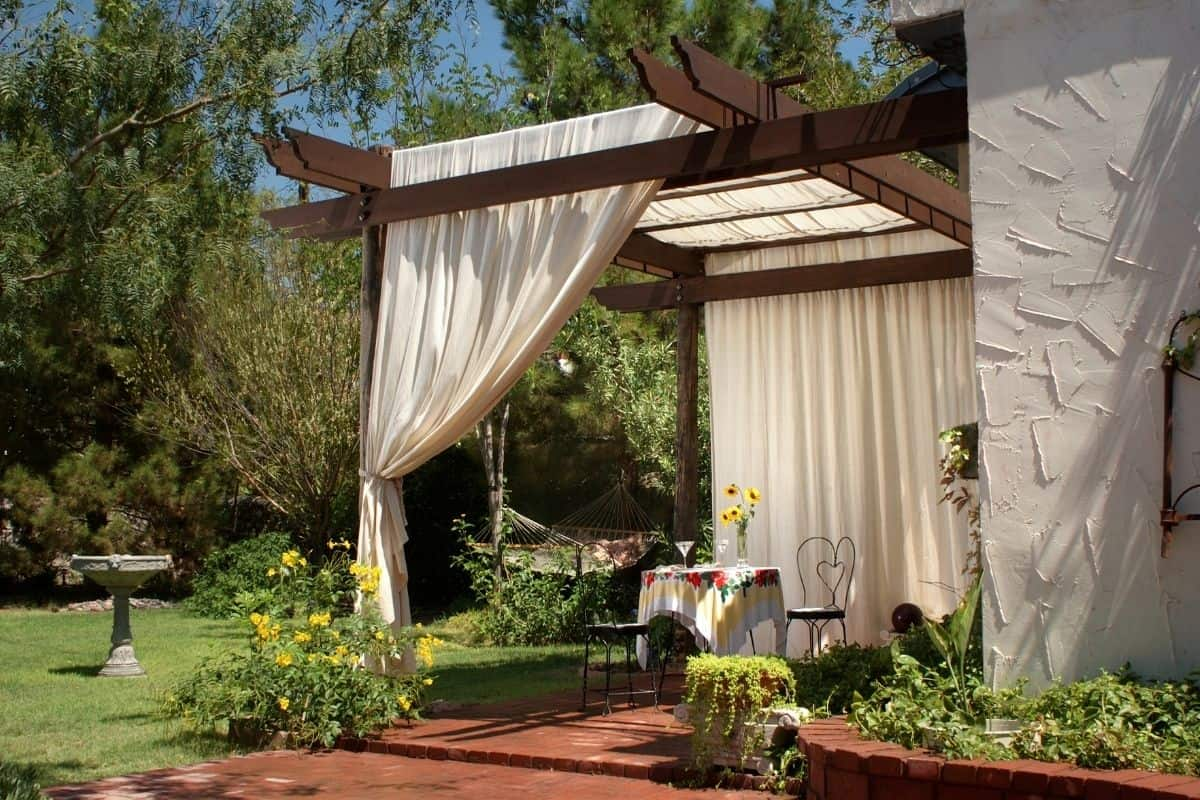 a romantic patio setting with a small table for two and white curtains