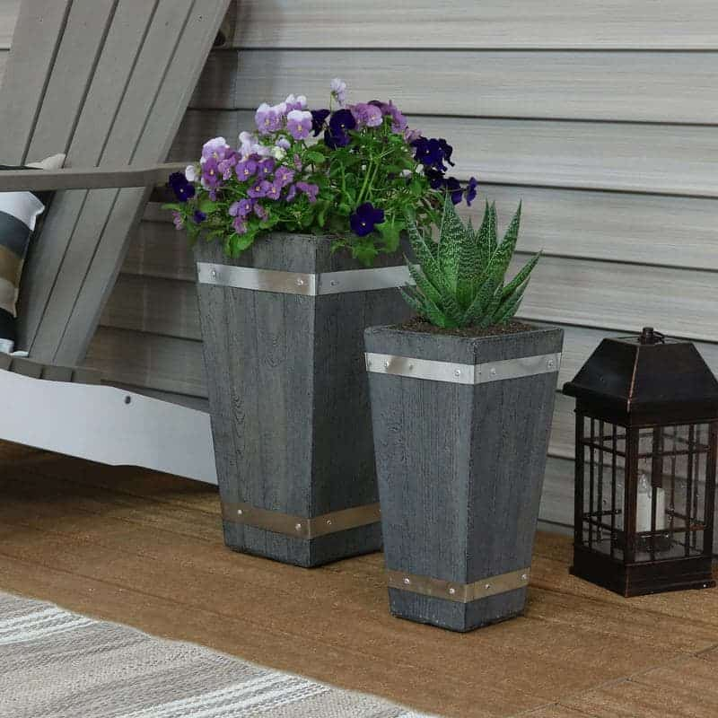 Gray tall planters in front of a wall