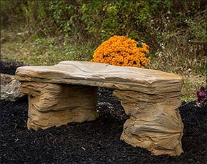 A bench made from solid rock and an orange flower bouquet behind it