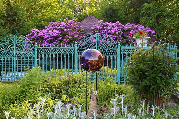 Gazing ball in front of a flower garden and fence
