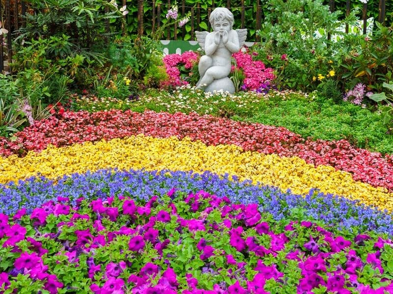 Garden angel surrounded by bright colored flowers