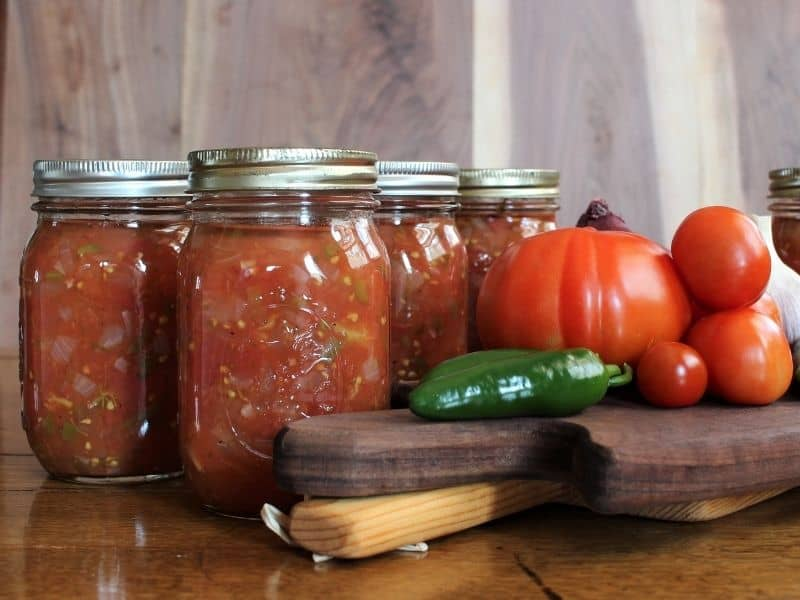 Canned salsa jars and tomatoes on a table