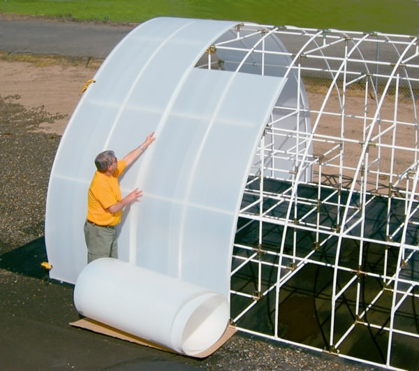 Man adding Solexx covering to his greenhouse frame