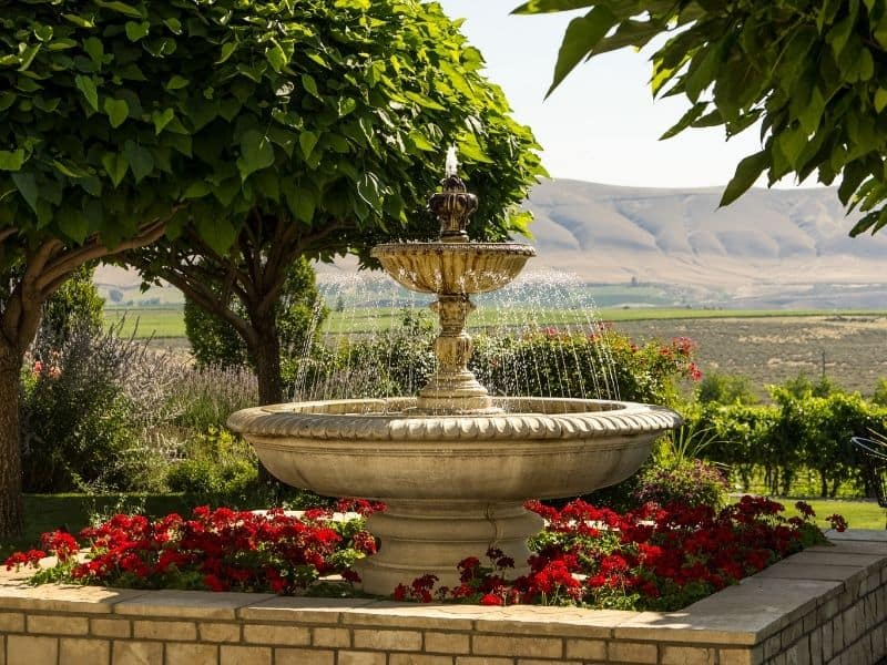 Garden fountain in the middle of a flower bed