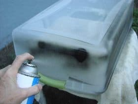 Spray painting the bin with black paint