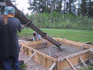Pouring concrete for the greenhouse base
