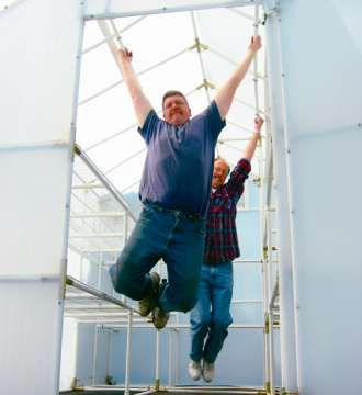 A couple of men hanging onto a Solexx greenhouse frame