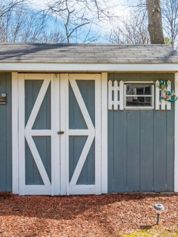 Storage shed painted gray with white accents