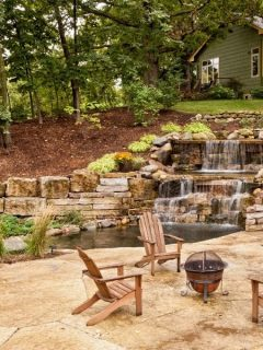 Backyard room with cascading watee, a fire pit and some chairs