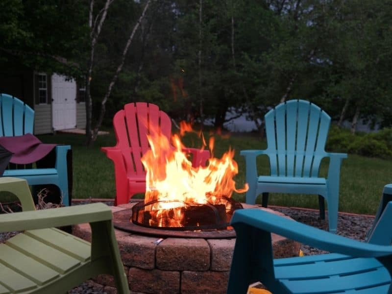 brick fire pit surrounded by lawn chairs