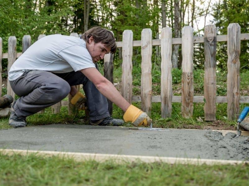 a man building a cement walkway