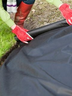 woman laying down weed barrier fabric