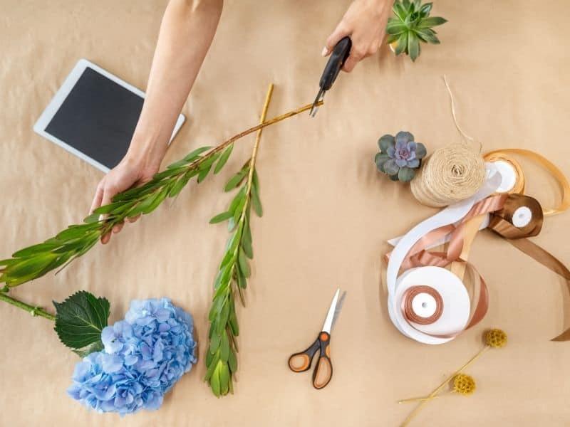 woman cutting flower stem diagonally