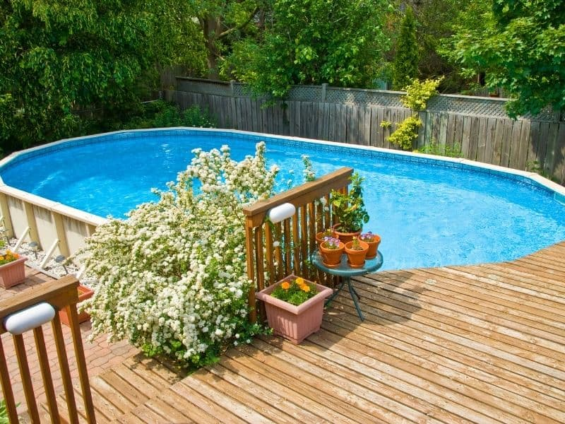 wooden deck and flowers next to a swimming pool