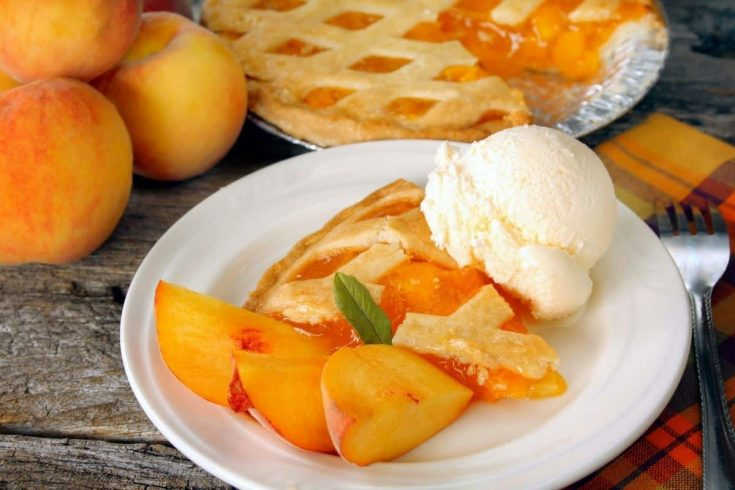 a piece of peach pie and a dollop of ice cream
