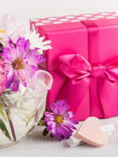 vase with pink flowers and gift wrapped in bright pink paper